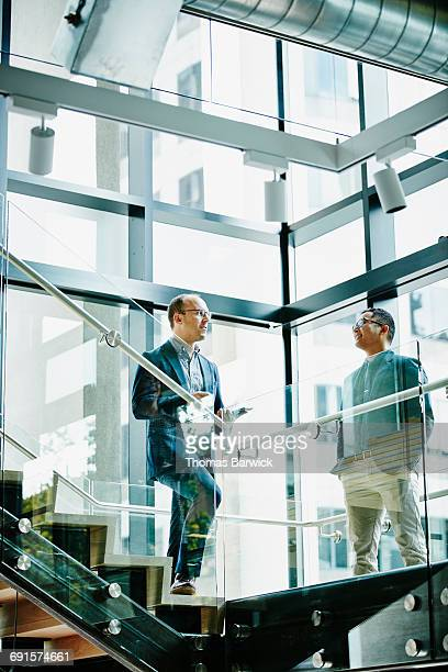 Businessmen in discussion on office stairs