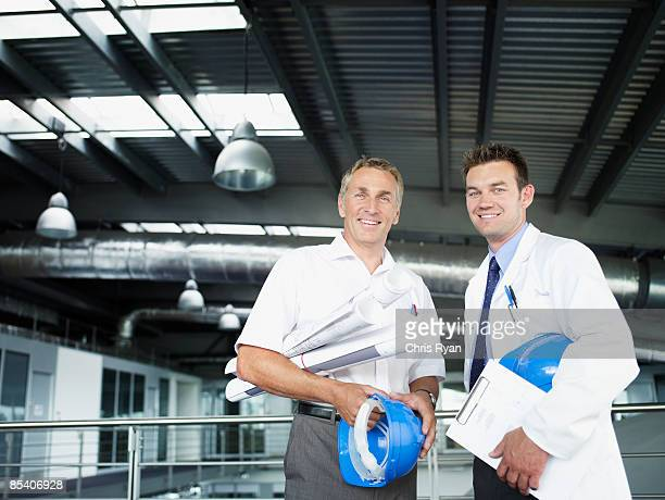 Businessmen in factory with blueprints