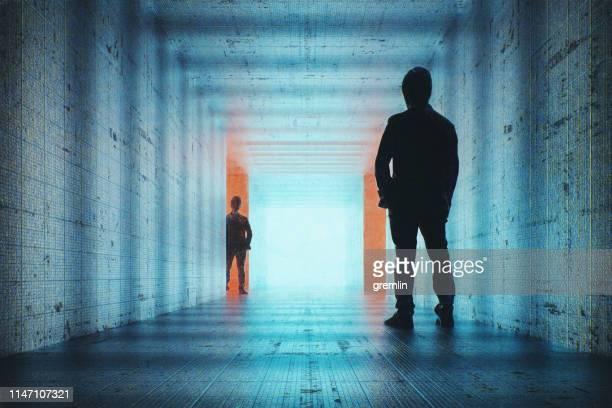 businessmen in futuristic underground corridor - stalker person stock photos and pictures