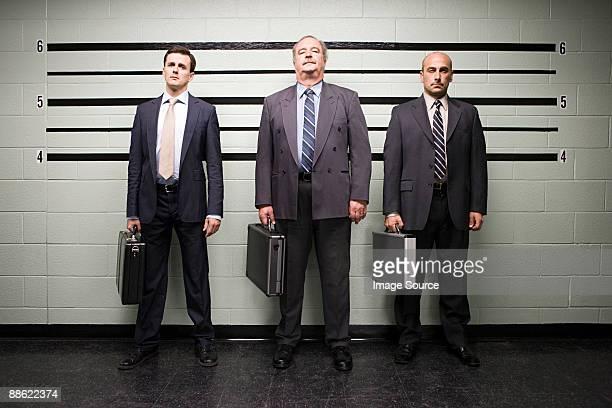 businessmen in lineup - confrontatie stockfoto's en -beelden