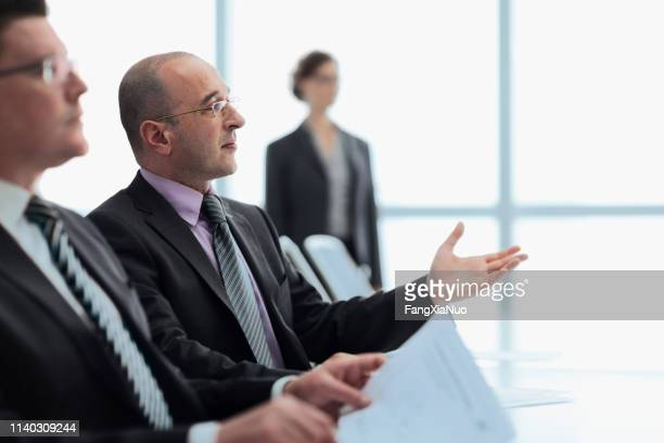 businessmen in meeting with colleagues in office - french culture stock pictures, royalty-free photos & images