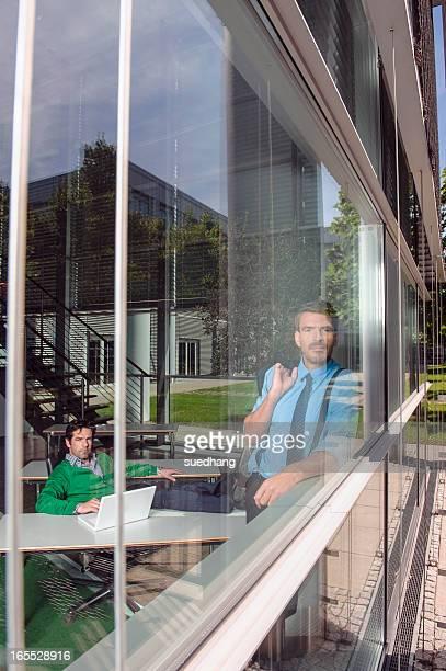 Businessmen in office behind window