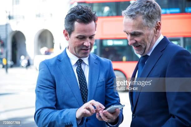 Businessmen in street looking at smartphone, London, UK