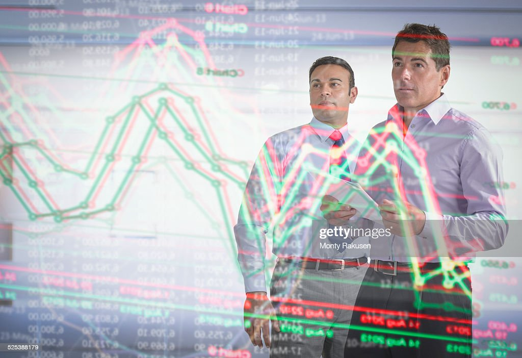 Businessmen inspecting graph on interactive futuristic display : Stock Photo