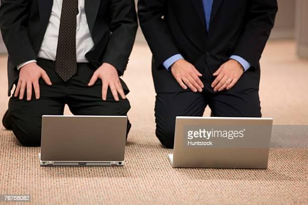 Businessmen kneeling on floor