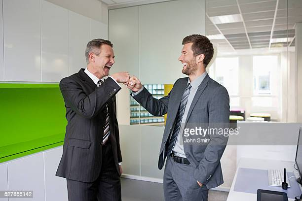 Businessmen laughing and bumping fists in office