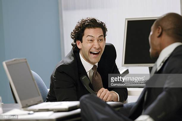 Businessmen laughing at work