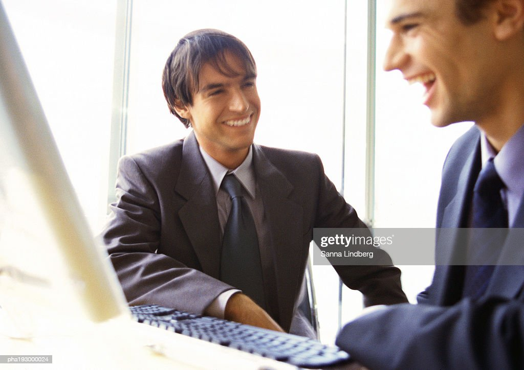 Businessmen laughing together, head and shoulders. : Stockfoto