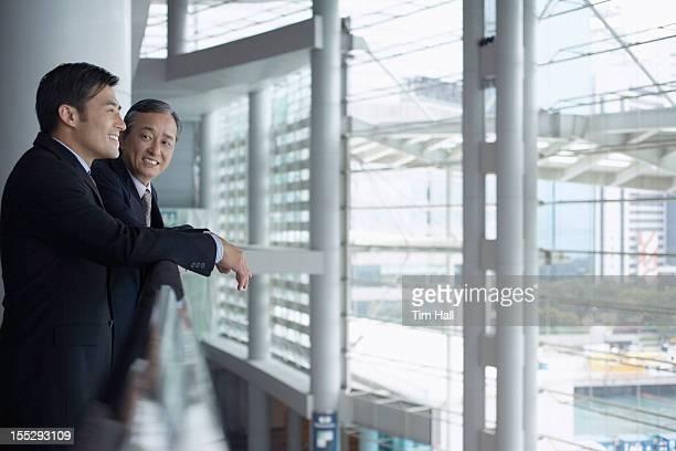 Businessmen leaning on banister