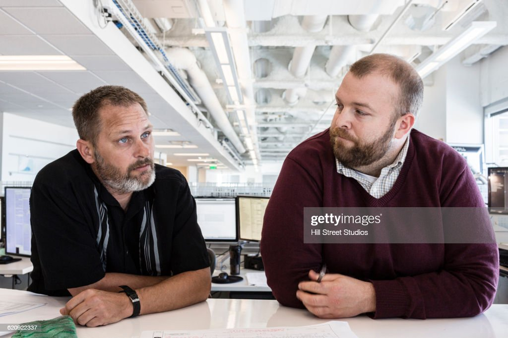 Businessmen listening in office meeting : Stock Photo