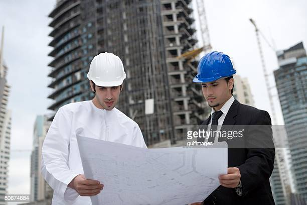 Businessmen looking at blueprint at construction site