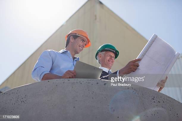 Geschäftsleute, die im Werkzeuge und mit Handy im Freien