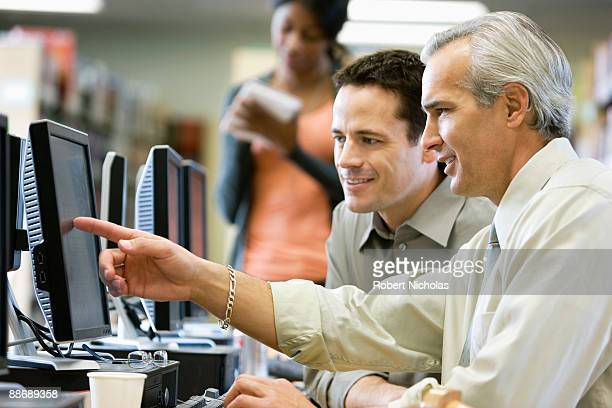 Businessmen looking at computer monitor