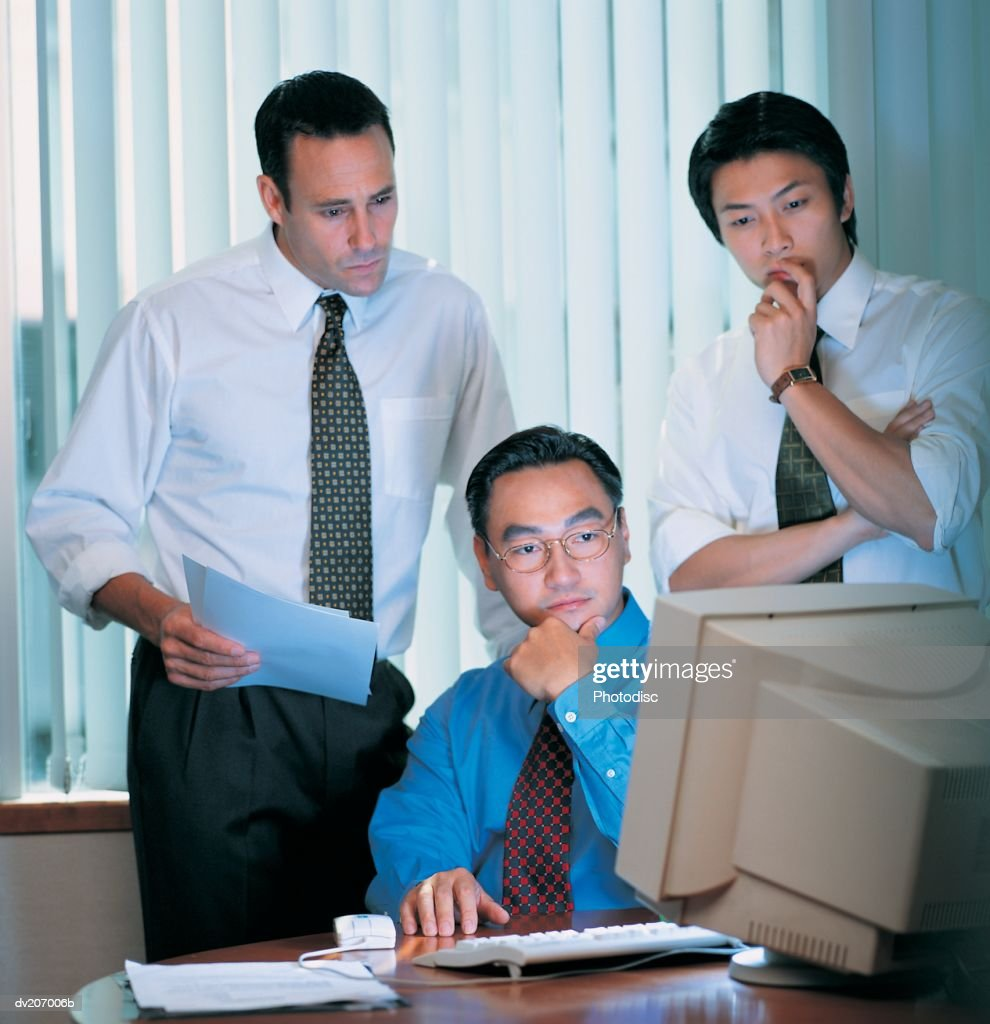 Businessmen looking at computer monitor : Stock Photo