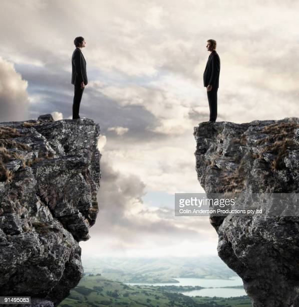 Businessmen looking at each other across chasm
