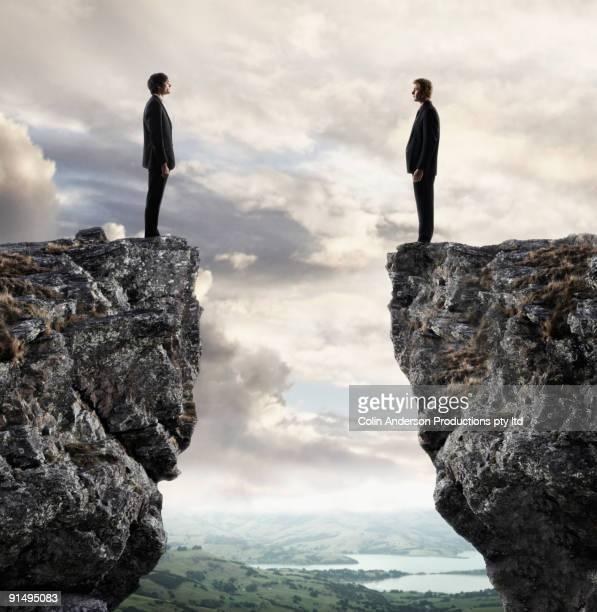 businessmen looking at each other across chasm - rivaliteit stockfoto's en -beelden