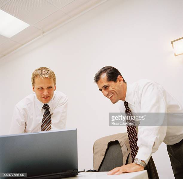 Businessmen looking at laptop computer screen