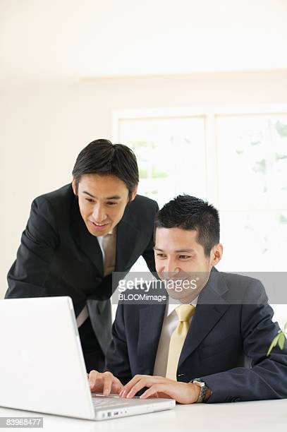 Businessmen looking at laptop PC screen