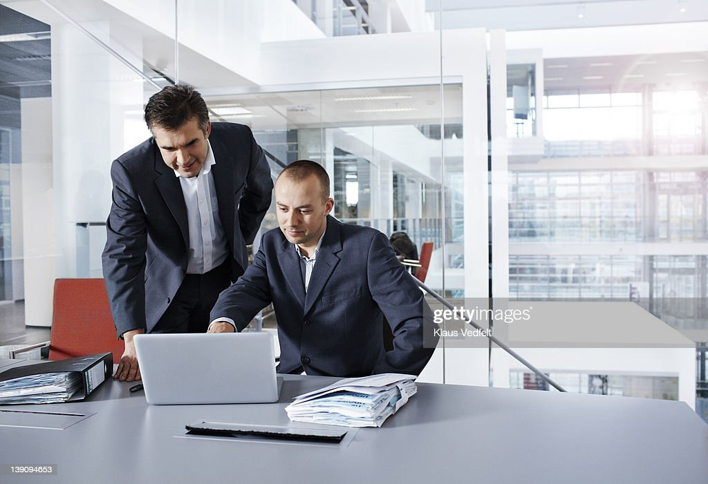 Businessmen looking at laptop : Stock Photo