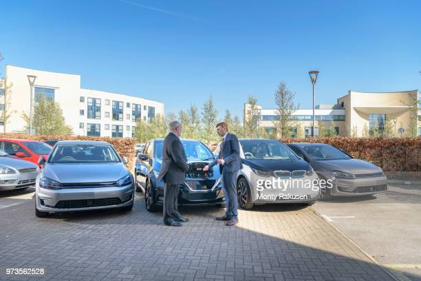 businessmen looking at range of electric cars in business park - electric car stock pictures, royalty-free photos & images