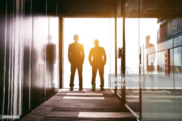 Businessmen looking out the office window