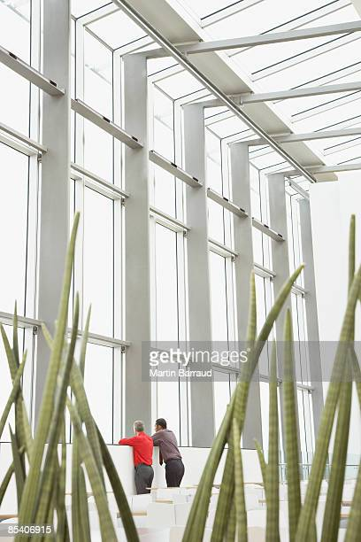 businessmen looking out window in cafe - public building stock pictures, royalty-free photos & images