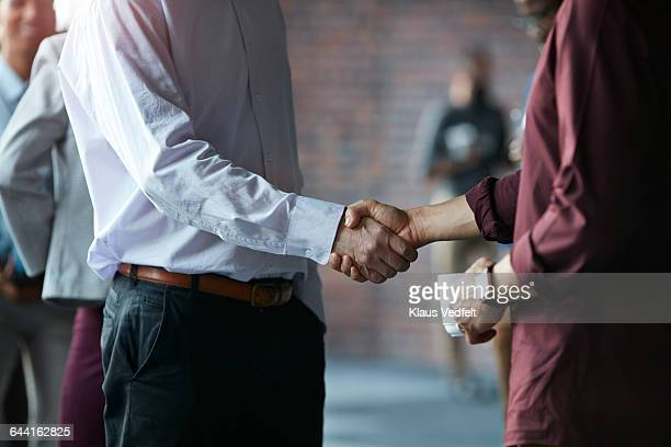 Businessmen making handshake at conference