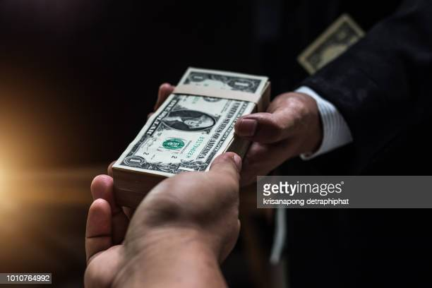 businessmen making handshake with money in hands, corruption and bribery concepts. - corruption stock pictures, royalty-free photos & images