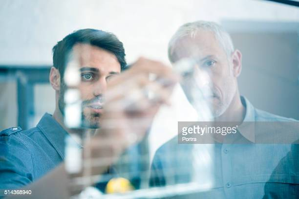 businessmen making plan on glass wall in office - business strategy stock photos and pictures
