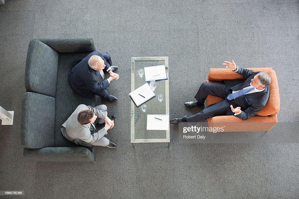 Businessmen meeting in lobby : Stock Photo