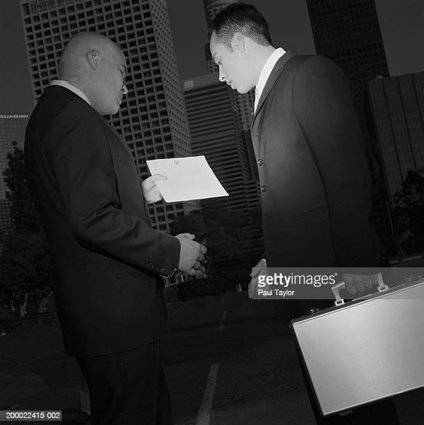 Businessmen meeting outdoors, looking at paperwork (B&W)