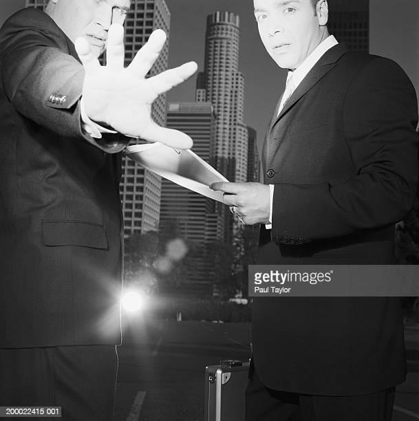 Businessmen meeting outdoors, man  extending hand (B&W)
