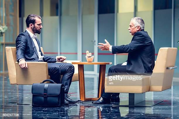 empresários negociação em um escritório moderno lobby - persuasão - fotografias e filmes do acervo