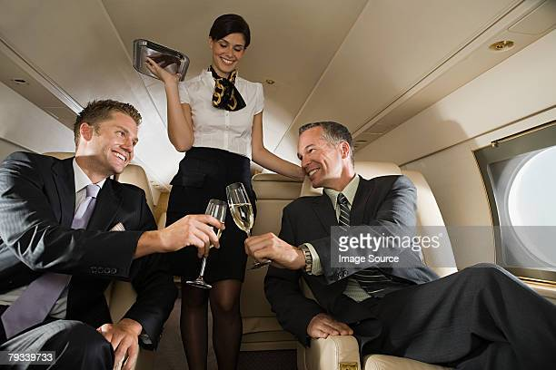 Businessmen on jet with champagne