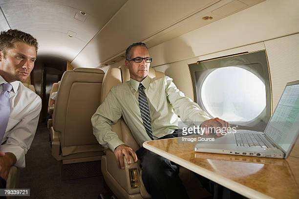 Businessmen on jet with laptop