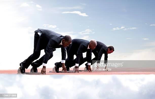 Businessmen on start line of running track,