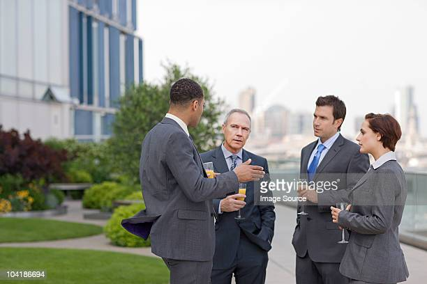 Businessmen outside with drinks