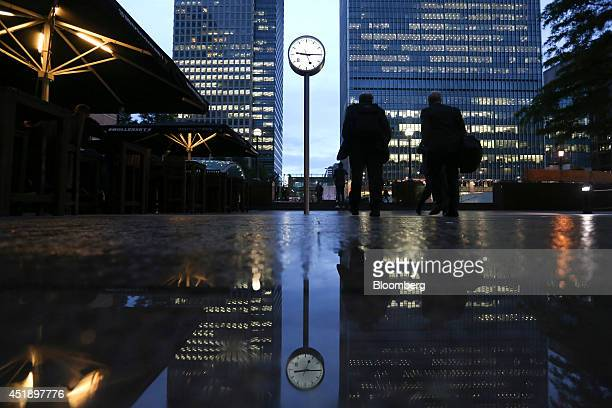 Businessmen pass an illuminated clock near the offices of global financial institutions in the Canary Wharf business finance and shopping district at...
