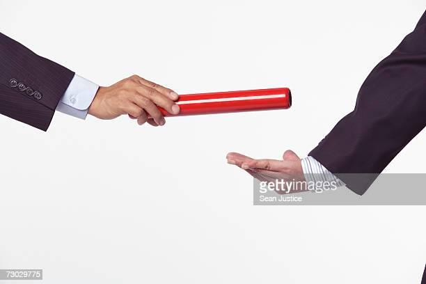 Businessmen passing baton, close-up