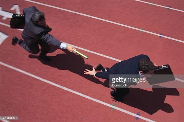 Businessmen passing baton during relay race