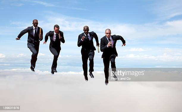 Businessmen passing baton to colleague in the sky