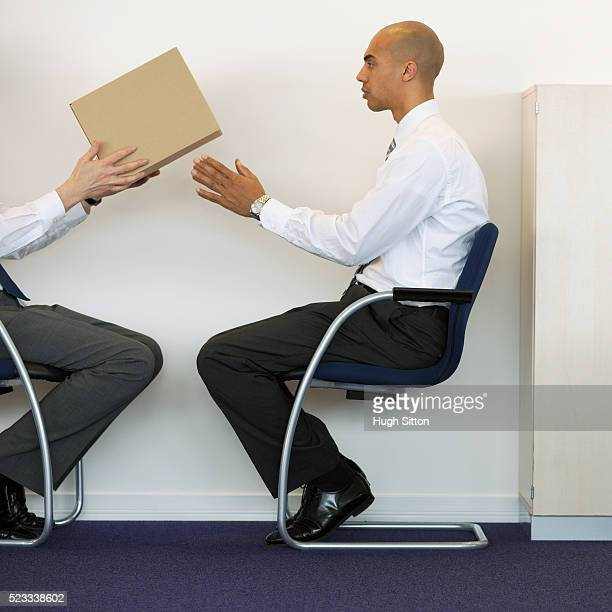 businessmen passing cardboard box - hugh sitton stock pictures, royalty-free photos & images