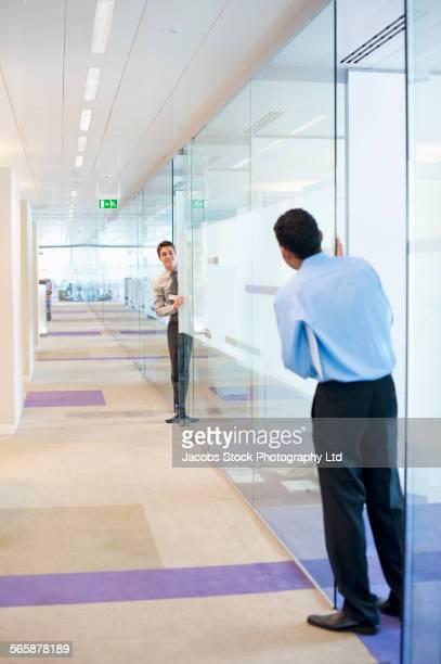Businessmen peeking around glass wall in office
