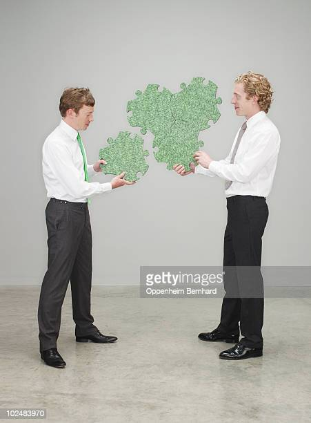businessmen piecing a green puzzle together - top bianco foto e immagini stock
