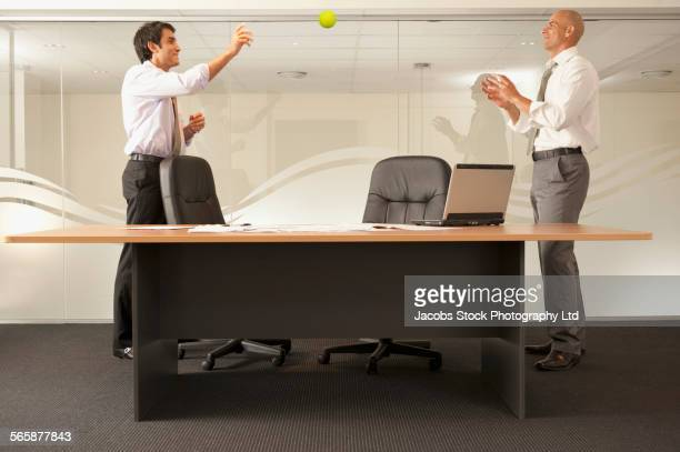 Businessmen playing catch in office