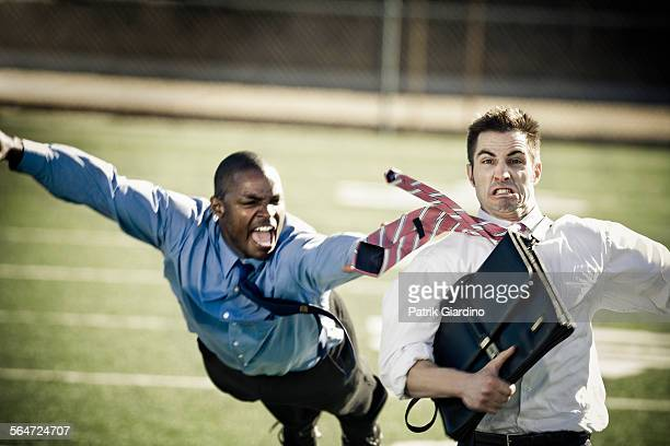 businessmen playing football - tackling stock pictures, royalty-free photos & images
