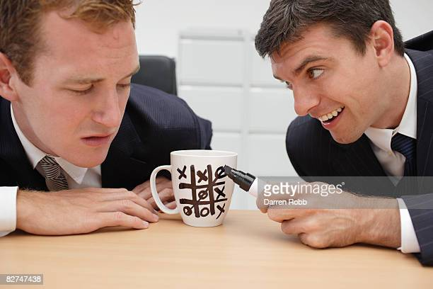 Businessmen playing Noughts and Crosses on mug