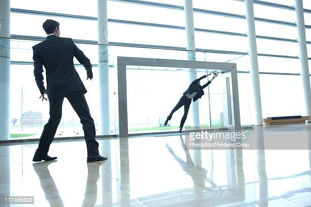 Businessmen playing soccer in lobby