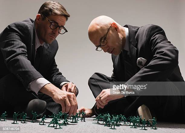 Businessmen Playing with Toy Soldiers