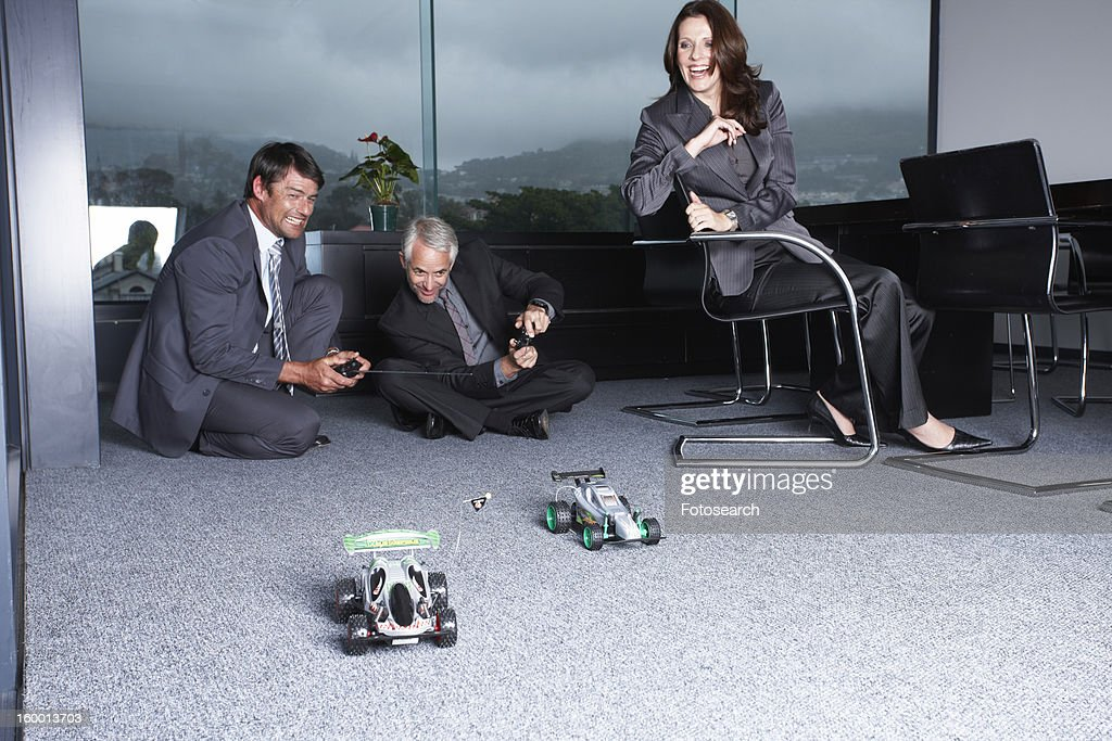 Businessmen playing with toys : Stock Photo